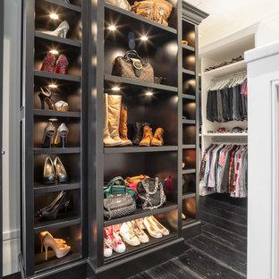 Foto de armario vestidor de mujer, clásico renovado, extra grande, con armarios abiertos, puertas de armario negras y suelo de madera oscura