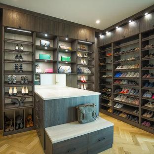 Exemple d'un très grand dressing room tendance neutre avec un placard à porte plane, des portes de placard en bois sombre, un sol en bois clair et un sol beige.