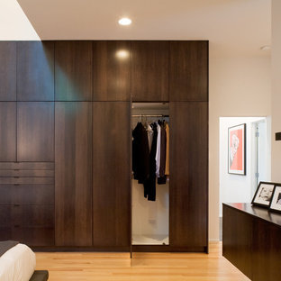 Reach-in closet - modern reach-in closet idea in Kansas City with flat-panel cabinets and dark wood cabinets