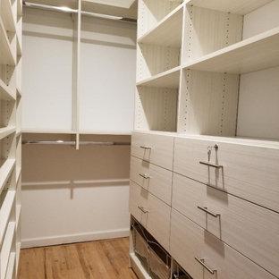 Modelo de armario vestidor unisex y abovedado, moderno, grande, con armarios con paneles lisos, puertas de armario de madera clara, suelo de madera clara y suelo beige