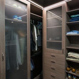 Ejemplo de armario vestidor de hombre y abovedado, minimalista, de tamaño medio, con armarios con paneles lisos, puertas de armario de madera oscura, suelo de baldosas de cerámica y suelo gris