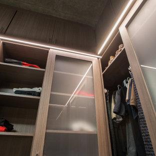Diseño de armario vestidor de hombre y abovedado, minimalista, de tamaño medio, con armarios con paneles lisos, puertas de armario de madera oscura, suelo de baldosas de cerámica y suelo gris