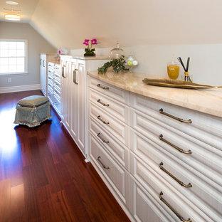 Esempio di un'ampia cabina armadio unisex tradizionale con pavimento in legno massello medio e pavimento rosso