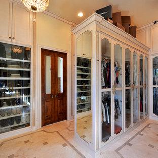Ispirazione per una grande cabina armadio unisex vittoriana con ante di vetro e ante beige