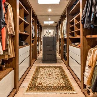 Modelo de armario vestidor unisex, contemporáneo, con armarios abiertos, puertas de armario de madera oscura, suelo de madera clara y suelo beige