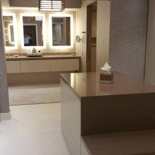 Ejemplo de vestidor unisex, moderno, grande, con armarios con paneles lisos, puertas de armario beige y suelo de piedra caliza