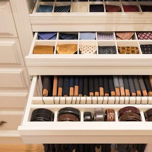 Modelo de vestidor clásico, extra grande, con armarios con paneles con relieve, puertas de armario beige, suelo de madera en tonos medios y suelo marrón