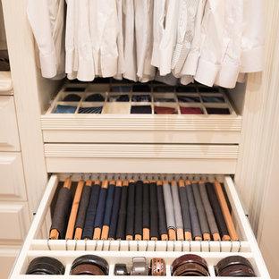 Ispirazione per un ampio spazio per vestirsi classico con ante con bugna sagomata, ante beige, pavimento in legno massello medio e pavimento marrone