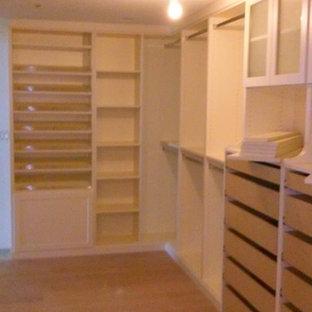 Imagen de armario vestidor unisex, clásico, grande, con armarios con paneles lisos, puertas de armario blancas y suelo de madera en tonos medios