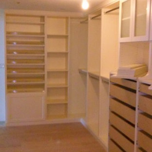 Photo of a large traditional gender-neutral walk-in wardrobe in Miami with flat-panel cabinets, white cabinets and medium hardwood floors.
