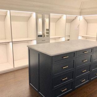 Modelo de armario vestidor unisex, clásico, grande, con armarios con paneles empotrados, puertas de armario azules y suelo de madera oscura
