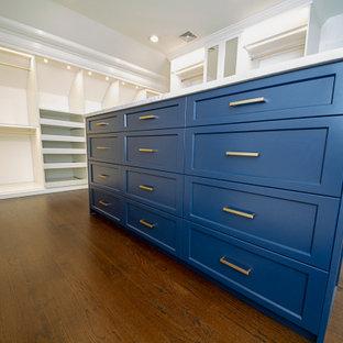 Imagen de armario vestidor unisex, tradicional, grande, con armarios con paneles empotrados, puertas de armario azules y suelo de madera oscura