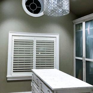 Ispirazione per una cabina armadio unisex american style di medie dimensioni con ante di vetro, ante con finitura invecchiata, pavimento in gres porcellanato e pavimento grigio