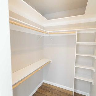 Modelo de armario vestidor unisex, clásico renovado, de tamaño medio, con puertas de armario blancas, suelo laminado y suelo marrón