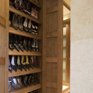 Photo of a contemporary standard wardrobe for women in London with medium wood cabinets.