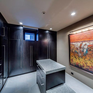 Large modern gender neutral dressing room in Calgary with flat-panel cabinets, dark wood cabinets and travertine flooring.
