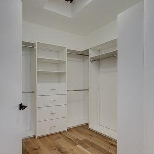 Cette image montre un petit dressing design neutre avec un placard sans porte et un sol en bois clair.