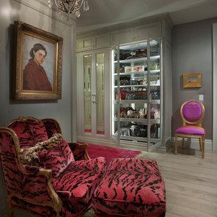 ロサンゼルスの女性用トランジショナルスタイルのおしゃれな収納・クローゼット (ガラス扉のキャビネット、グレーのキャビネット、淡色無垢フローリング) の写真