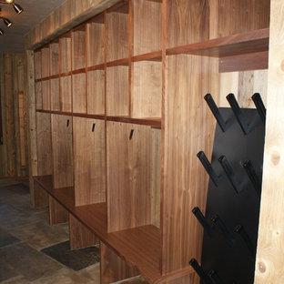 Inspiration för stora klassiska omklädningsrum för könsneutrala, med skåp i mellenmörkt trä, öppna hyllor och skiffergolv
