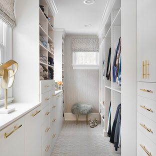 Design ideas for a transitional women's walk-in wardrobe in New York with carpet, flat-panel cabinets, white cabinets and grey floor.