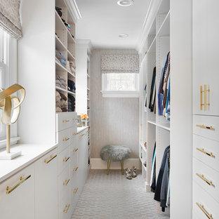 ニューヨークの女性用トランジショナルスタイルのおしゃれなウォークインクローゼット (カーペット敷き、フラットパネル扉のキャビネット、白いキャビネット、グレーの床) の写真