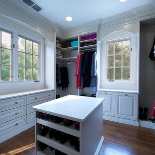 Foto di un'ampia cabina armadio per donna chic con ante con bugna sagomata, ante bianche e parquet chiaro