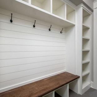 Modelo de armario y vestidor unisex, campestre, de tamaño medio, con armarios abiertos, puertas de armario blancas, suelo de baldosas de cerámica y suelo gris