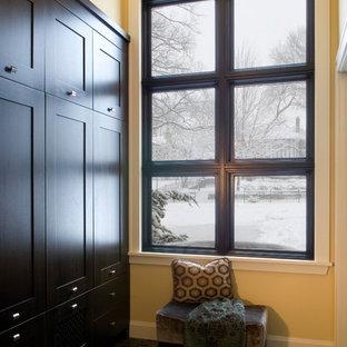 Imagen de armario y vestidor tradicional renovado, de tamaño medio, con armarios con paneles empotrados, puertas de armario negras y suelo de pizarra