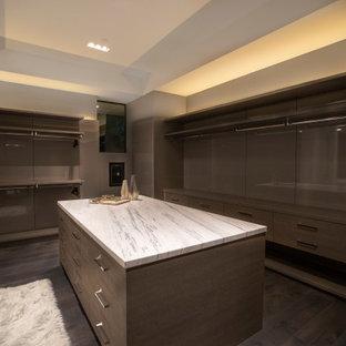 Imagen de armario vestidor unisex, minimalista, grande, con armarios abiertos, puertas de armario marrones, suelo de madera oscura y suelo marrón