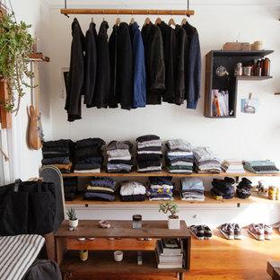 Imagen de armario y vestidor de hombre, bohemio, pequeño, con armarios abiertos y suelo de madera en tonos medios