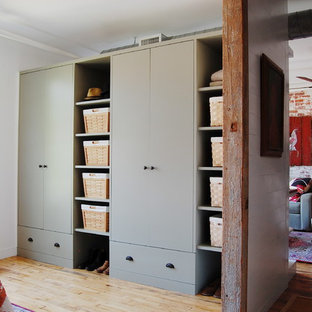 Design ideas for an industrial storage and wardrobe in New York with light hardwood floors.