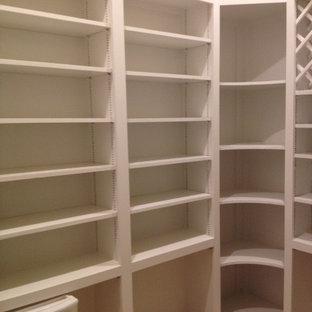 Imagen de armario vestidor unisex, contemporáneo, de tamaño medio, con armarios abiertos, puertas de armario blancas, suelo de travertino y suelo beige