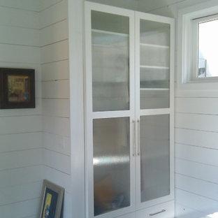 Aménagement d'un petit placard dressing contemporain neutre avec un placard à porte vitrée, des portes de placard blanches et un sol en bois foncé.