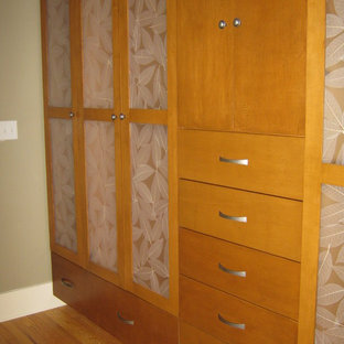 Inspiration for a large contemporary gender-neutral walk-in wardrobe in Other with shaker cabinets, white cabinets and light hardwood floors.