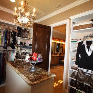 Ejemplo de armario vestidor de mujer, mediterráneo, de tamaño medio, con armarios abiertos, puertas de armario blancas y suelo de travertino