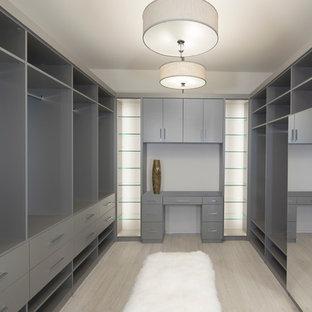 Ejemplo de armario vestidor unisex, contemporáneo, grande, con armarios abiertos, puertas de armario grises y suelo de madera clara