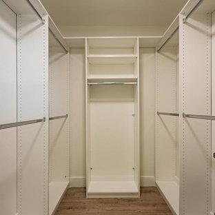 Cette photo montre un petit dressing bord de mer neutre avec un placard à porte shaker, des portes de placard blanches, un sol en carrelage de céramique et un sol marron.