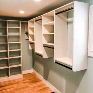 Ispirazione per una cabina armadio unisex american style di medie dimensioni con nessun'anta, ante in legno chiaro, parquet chiaro e pavimento arancione