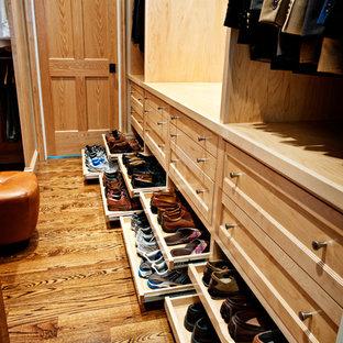 Immagine di un ampio spazio per vestirsi per uomo chic con ante in legno chiaro, ante con riquadro incassato e pavimento in legno massello medio