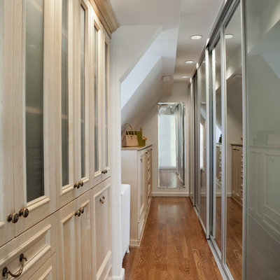 Large elegant gender-neutral medium tone wood floor dressing room photo in New York with recessed-panel cabinets and light wood cabinets
