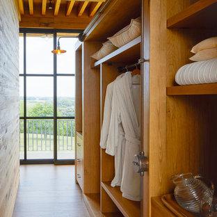 Exemple d'un placard dressing montagne neutre avec un placard sans porte, des portes de placard en bois brun, un sol en bois brun et un sol marron.