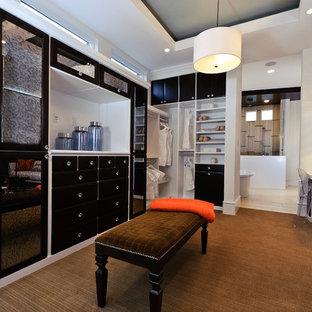 Пример оригинального дизайна: большая гардеробная комната унисекс в стиле современная классика с черными фасадами, ковровым покрытием, плоскими фасадами и коричневым полом