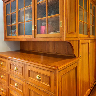 Example of a classic gender-neutral medium tone wood floor walk-in closet design in New York with beaded inset cabinets and medium tone wood cabinets
