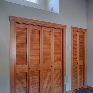 Modelo de armario unisex, contemporáneo, de tamaño medio, con armarios con puertas mallorquinas, puertas de armario de madera oscura y suelo de cemento