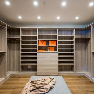 Imagen de vestidor unisex, contemporáneo, grande, con armarios con paneles lisos, puertas de armario de madera oscura, suelo de madera en tonos medios y suelo marrón