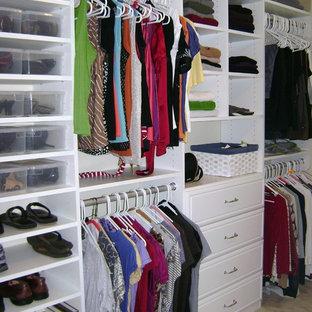 Imagen de armario vestidor unisex, tradicional, de tamaño medio, con armarios con paneles lisos, puertas de armario blancas y suelo de madera clara
