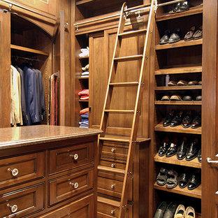 Ejemplo de vestidor de hombre, clásico, grande, con armarios con rebordes decorativos, puertas de armario de madera oscura y suelo de madera en tonos medios