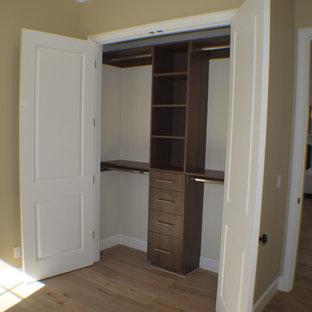 Diseño de armario unisex, clásico, pequeño, con armarios estilo shaker, puertas de armario de madera en tonos medios, suelo de madera clara y suelo marrón