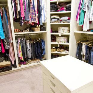Idée de décoration pour un grand dressing room craftsman neutre avec un placard à porte plane, des portes de placard blanches et moquette.
