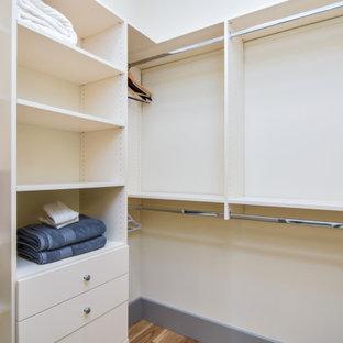 Modelo de armario vestidor unisex, mediterráneo, de tamaño medio, con armarios abiertos, puertas de armario blancas, suelo de baldosas de cerámica y suelo beige